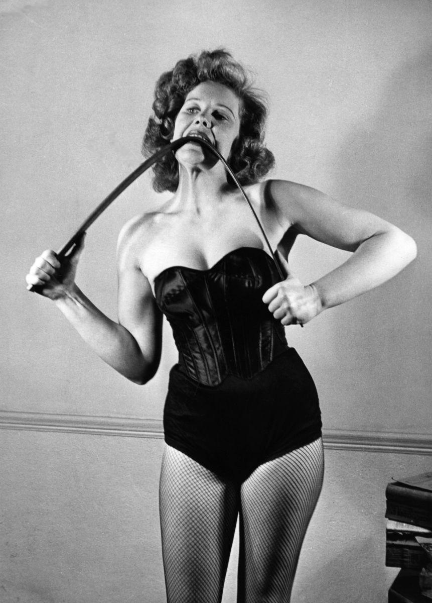 Strongwoman Joan Rhodes bends an iron bar between her teeth