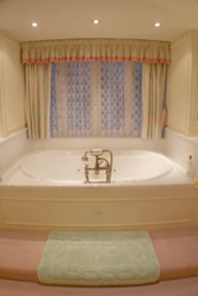 Soft, neutral colors and lace paired with splashes of color are used to create a quiet effect in this bath.