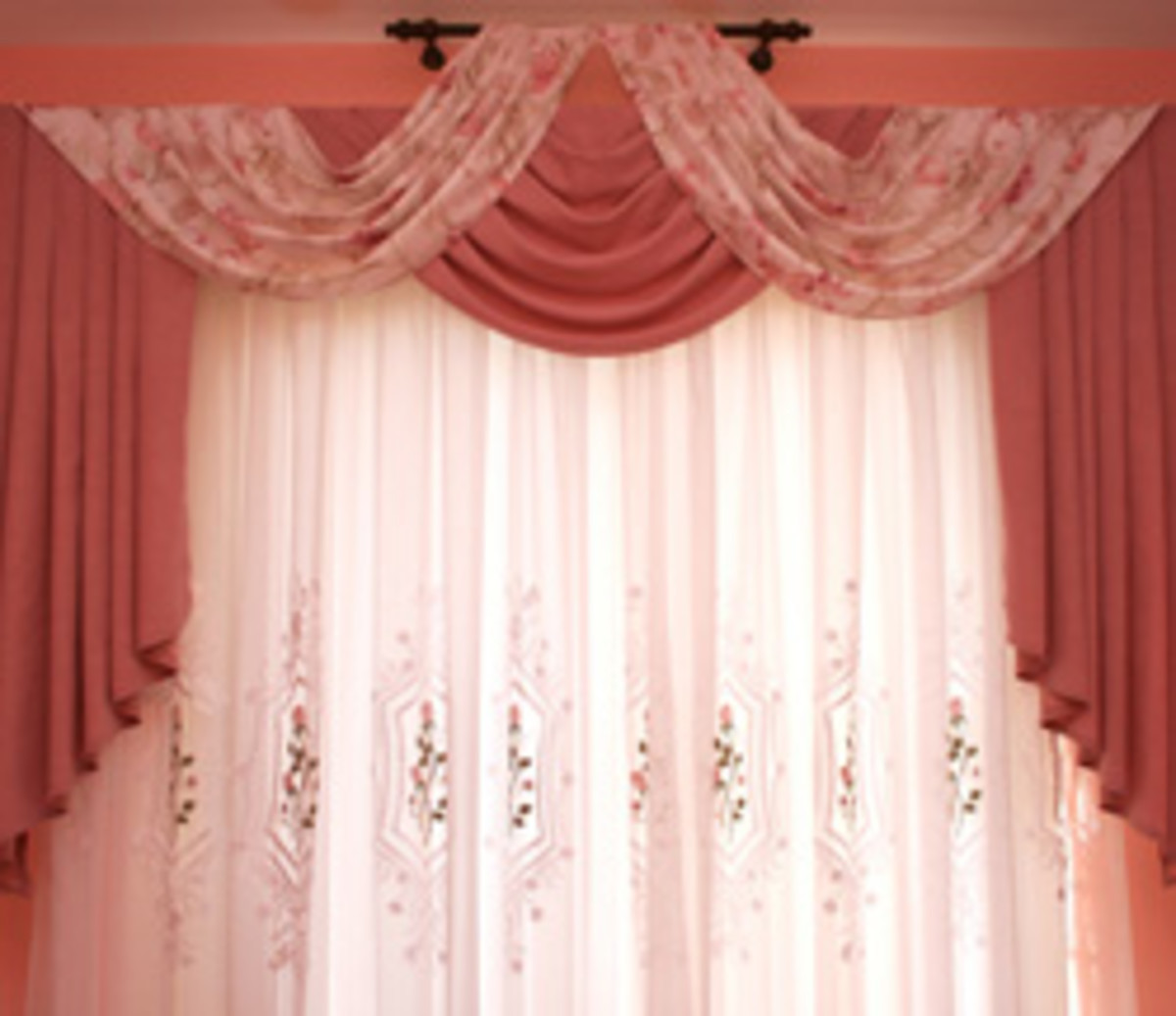 Colorful window scarves are draped over this sheer to create a stunning effect.