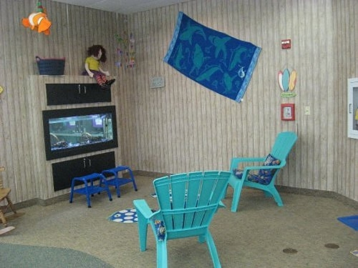 Plastic beach chairs provide seating where a parent can sit to read to a child. The aquarium adds visual interest and serves to divide the children's computer area from the seating area.