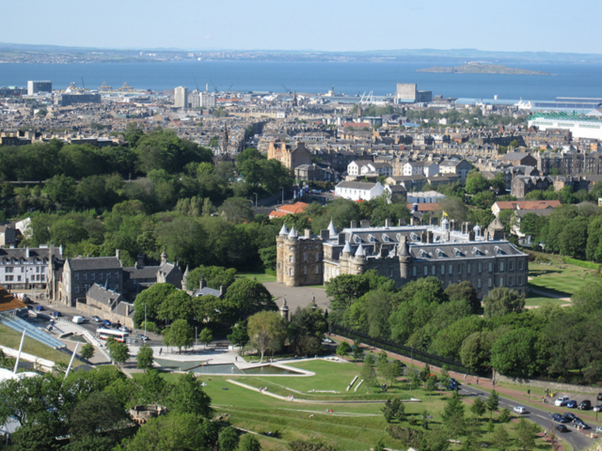 Holyrood Palace, Edinburgh,  the official royal residence in Scotland, with the blue waters of the Firth of Forth shining int he distance.