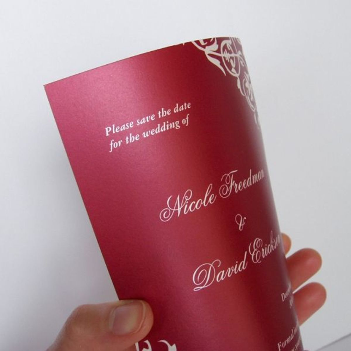 Festive red scroll save the date card printed on Zazzle metallic champagne color paper