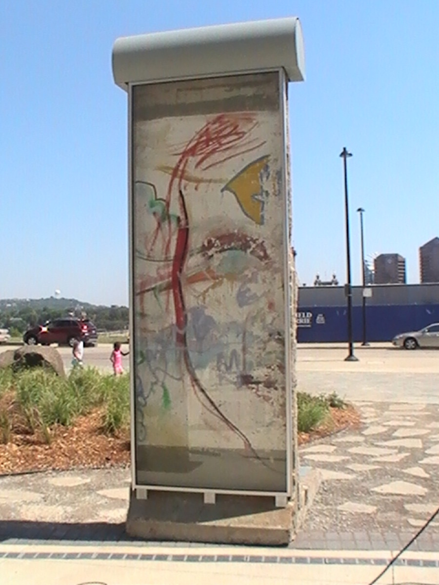 Cincinnati's Berlin Wall Monument stands with the painted side facing the Freedom Center Building. The plain white side faces the Ohio River. Both the river and the Berlin Wall played important roles in the history of freedom.