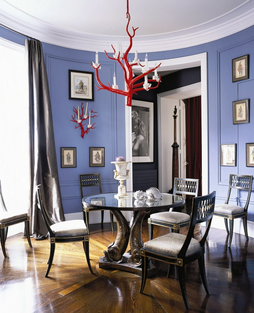 A circular, Paris dining room with periwinkle blue walls and a coral chandelier.