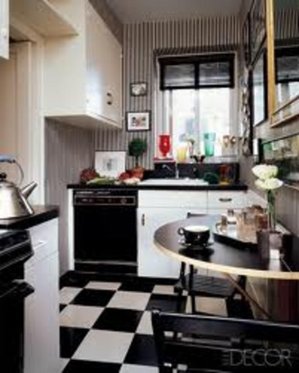 A tiny, New York kitchen featuring a hinged, drop-leaf table and painted folding chairs.