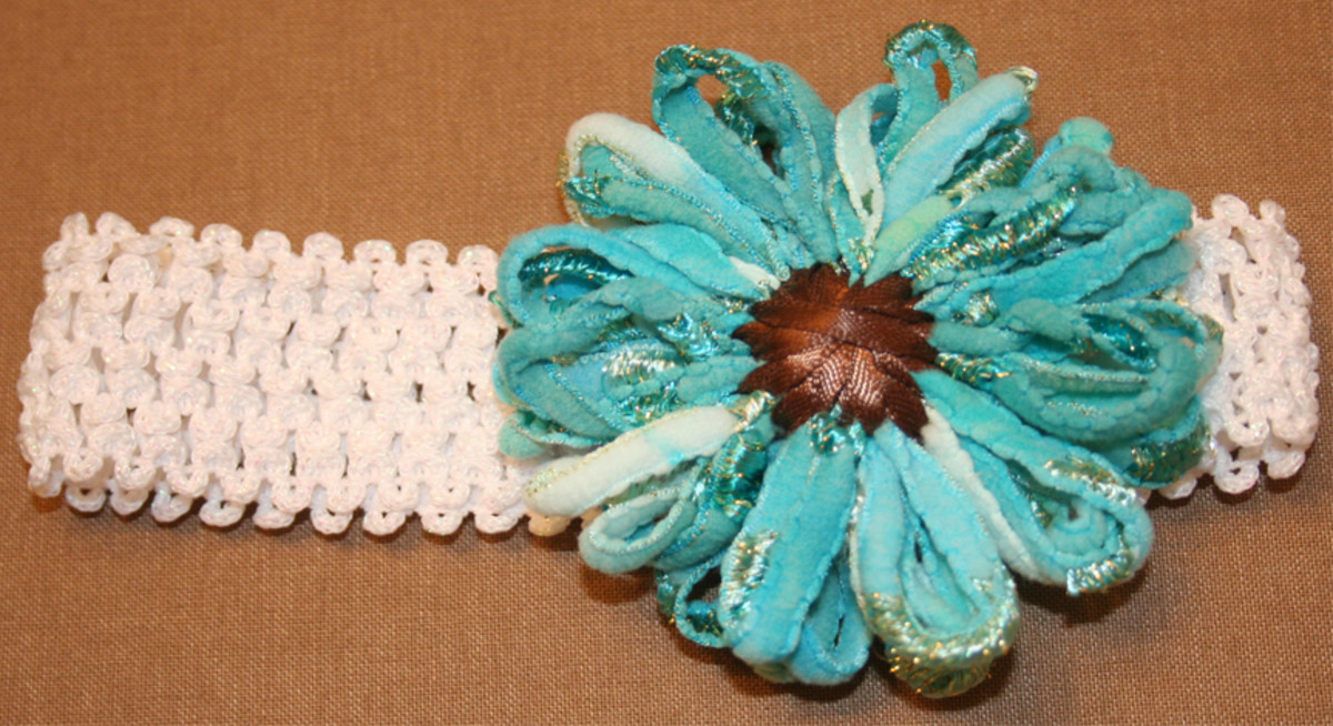 Flower made from funky yarn and brown ribbon on a Knifty Knitter Loom.
