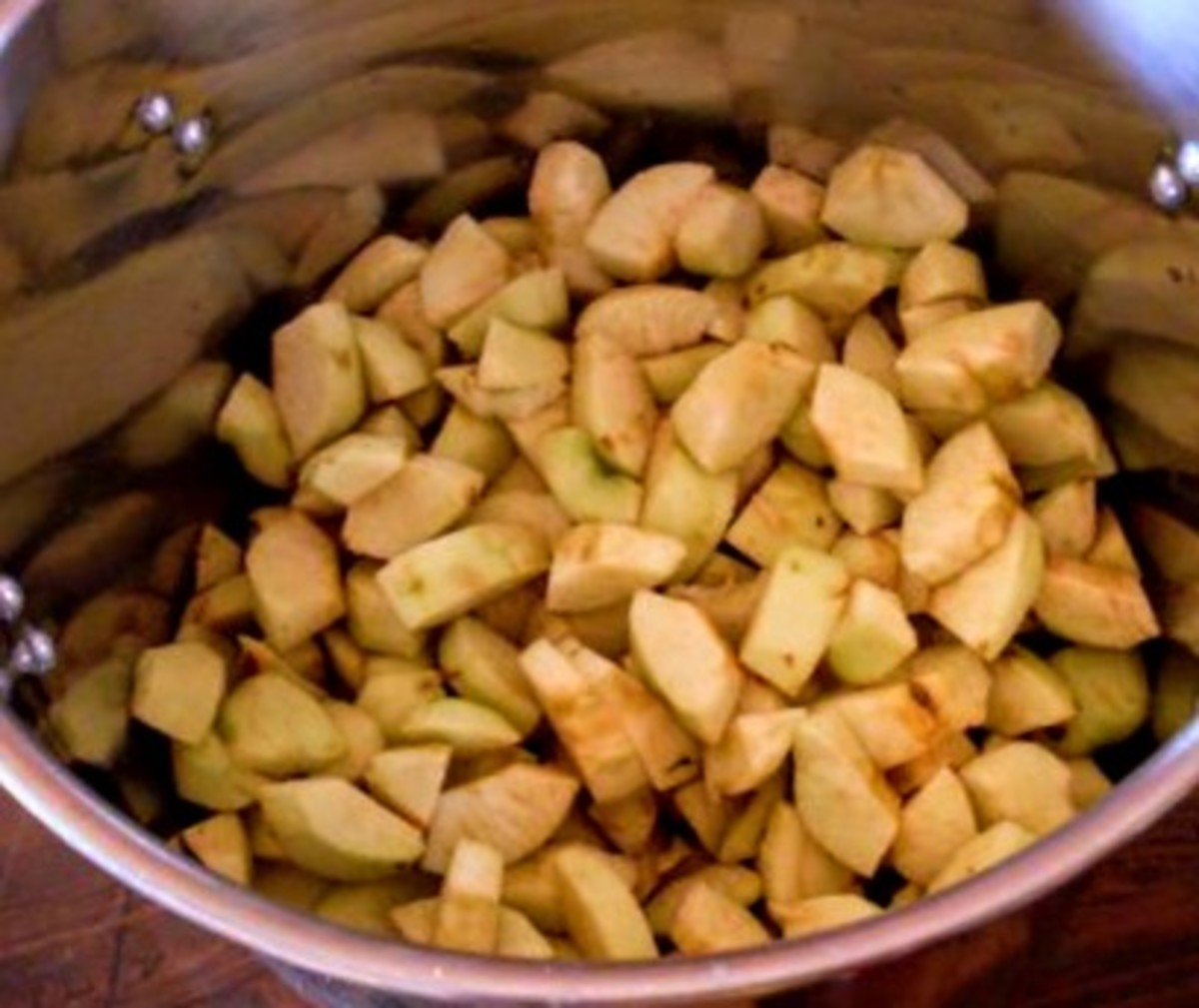 Slice apples into cooking pot. Cut any shape or style you desire, keeping in mind that smaller pieces will fall apart easier during the heat processing to come.
