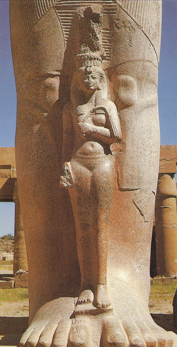 The dimunitive figure of a graceful queen Nefertari standing between the legs of the colossal granite state of Ramesses II in the first courtyard of the temple at Karnak; maybe his daughter Bint-Anath, whose mother was Istnofret