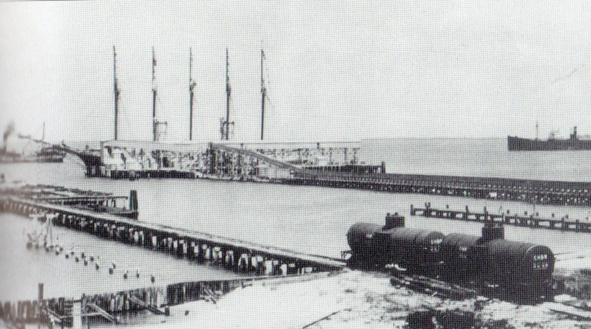 "Boca Grande phosphate dock, Circa 1915, is a massive conveyor belt. The phosphate is unloaded at the railhead and carried by the belt to the ship. Note the ship being loaded is a five masted ""Yankee Schooner,"" replaced by steamships by the 1920s."