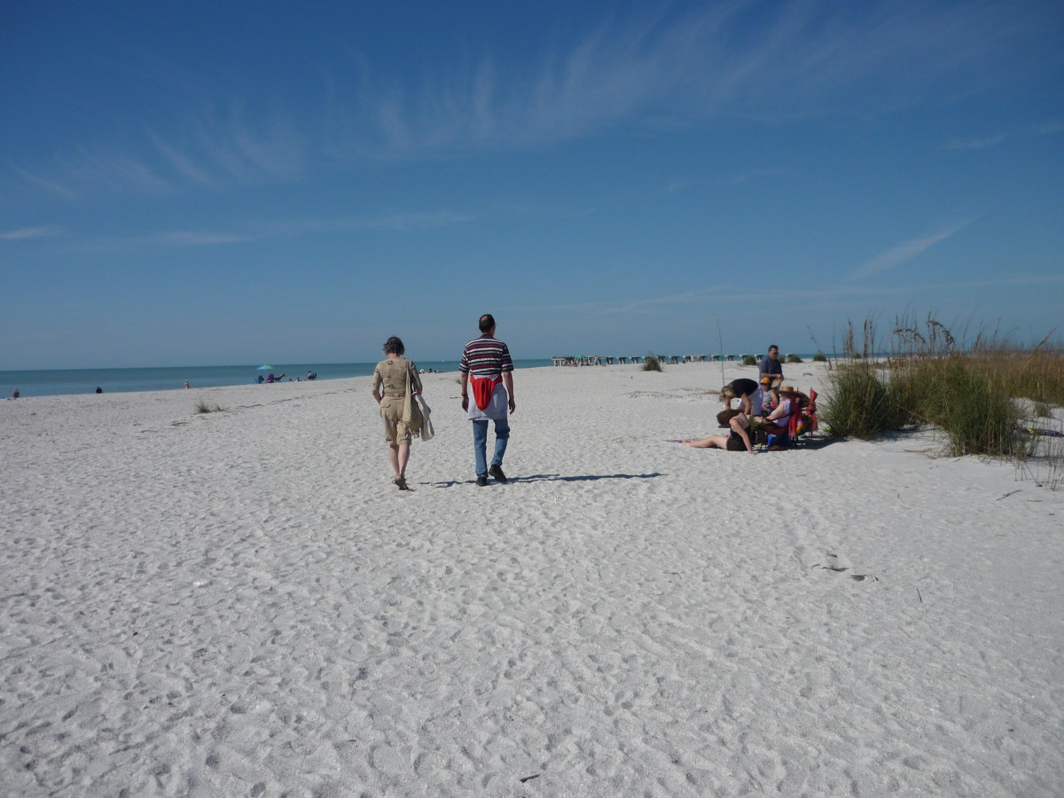 My husband and I walking on the beautiful white sand beach on our way to ....