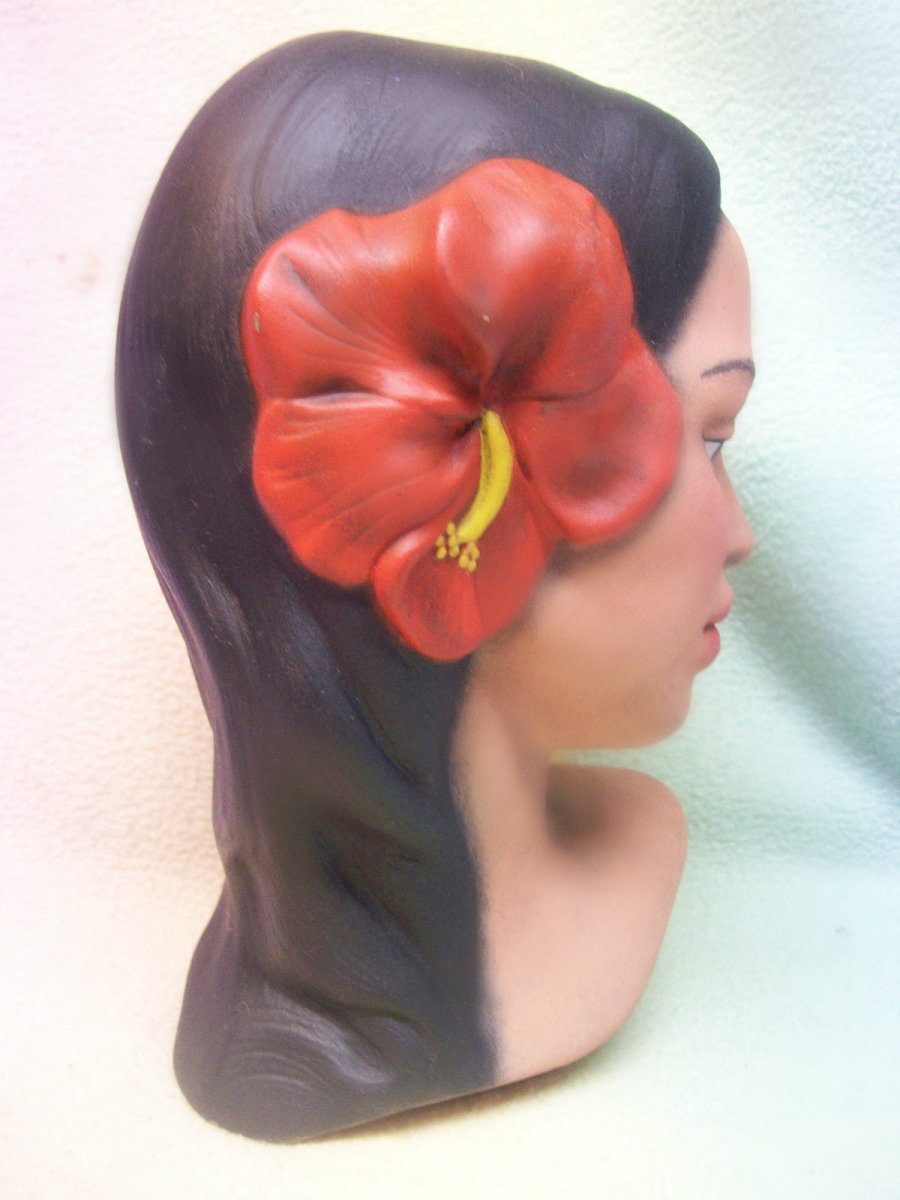 She is a beauty with long black hair adorned with two pretty soft red hibiscus flowers along one side of her head. Her lips are a flesh tone. This is a beautiful example of a handmade, and made in Hawaii Polynesian girl head bust.