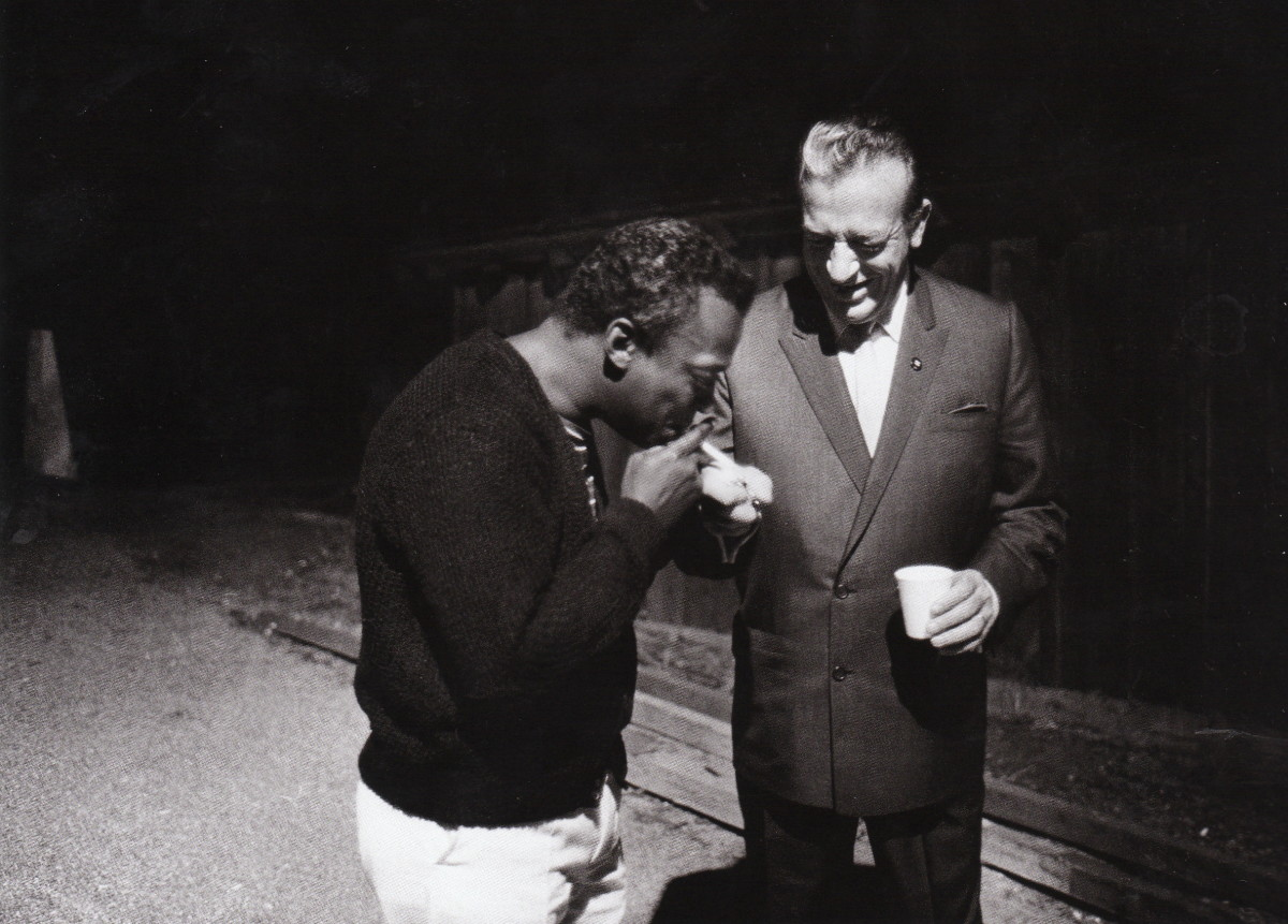 Miles Davis having a cigarette lit by Harry James on the backstage at the Monterey Jazz Festival 1963.