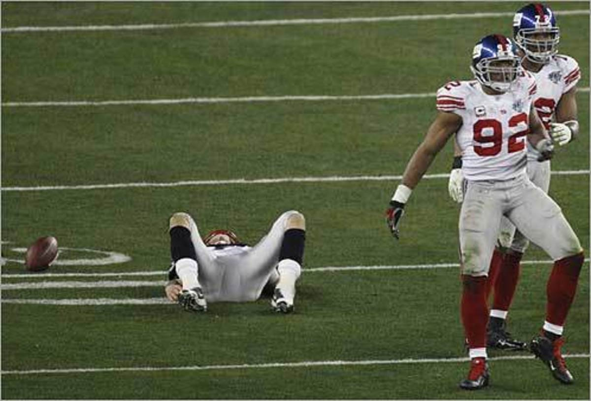 Patriots Tom Brady got sacked in the third quarter and New York Giants' Michael Strahan (92) and Osi Umenyiora (72) celebrated the sack. New England Patriots played against the New York Giants in Super Bowl XLII on Sunday, Feb. 3 in the University o