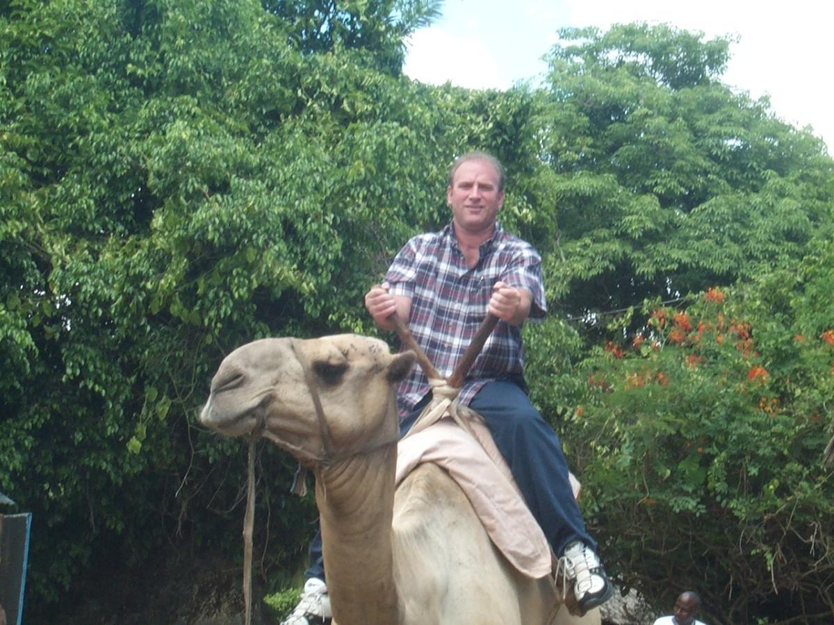 Clark Rone riding a camel in Kenya