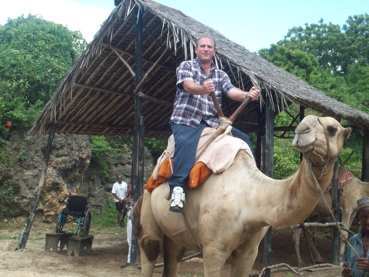 Clark Rone riding a camel in Kenya with his wheelchair on benches in the background.