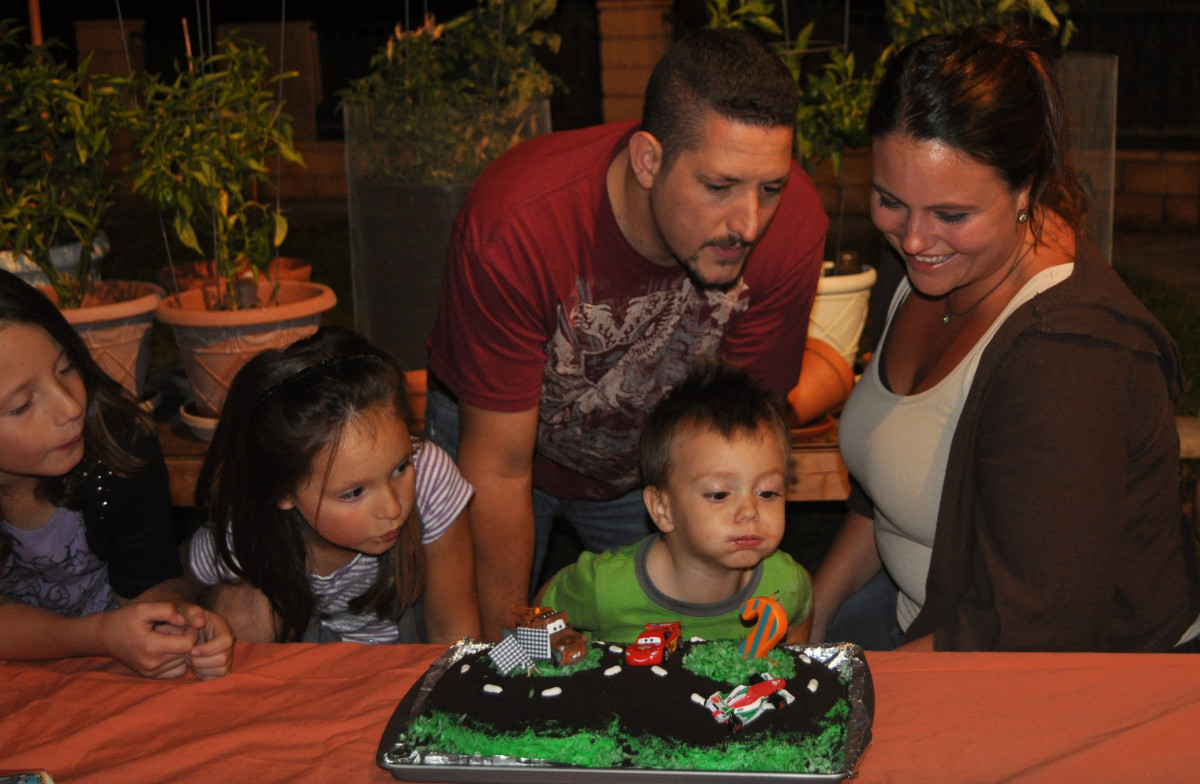 The entire family gathered around to help Max blow out his candle.