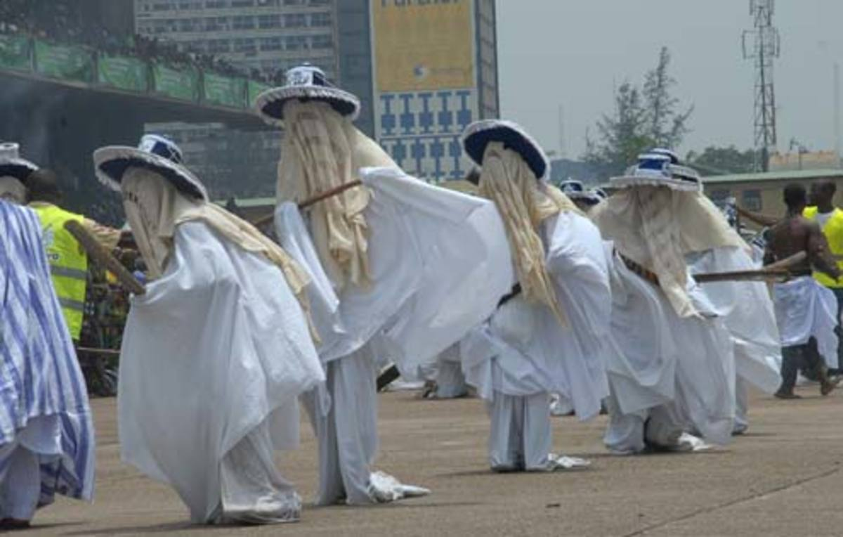 A typical procession of the Eyo masquerades dancing and moving along through the streets of Lagos Island.