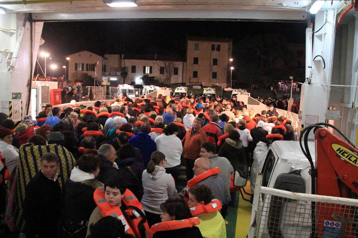 Passengers arrive on shore in lifevests and blankets