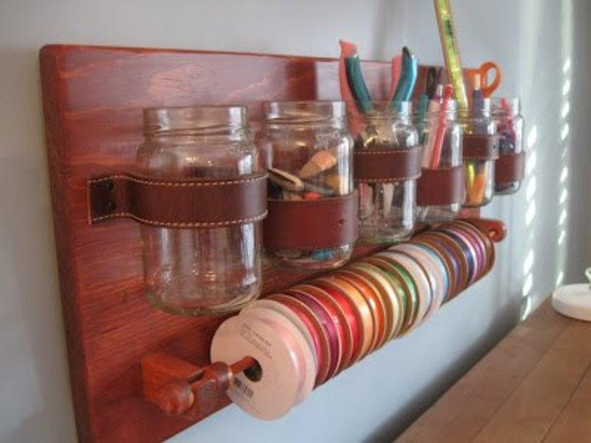 Kristen and her husband created a wall mount craft storage unit with mason type jars, repurposed belts, and a dowel for ribbon.