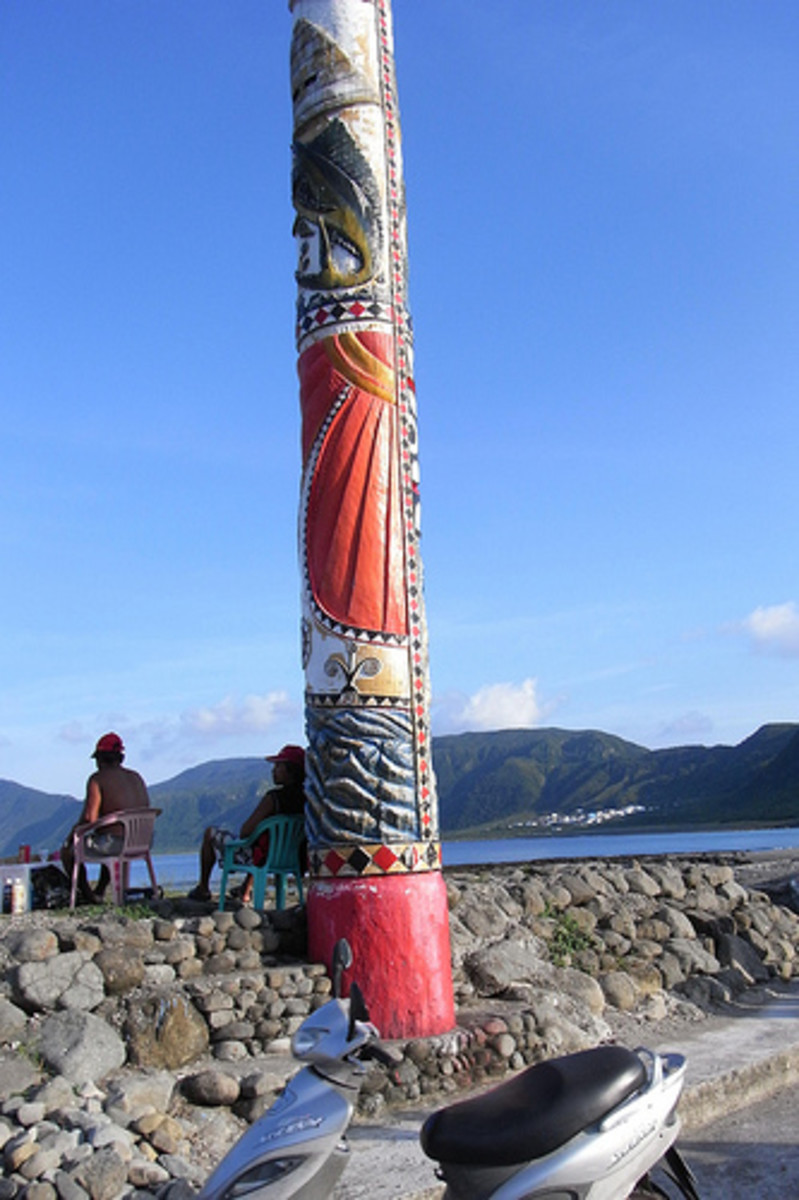This carved pole appears to be near the shoreline recreation area for tourists. Carved poles were usual in the Eastern Hemisphere before they began appearing in the Pacific Northwest.