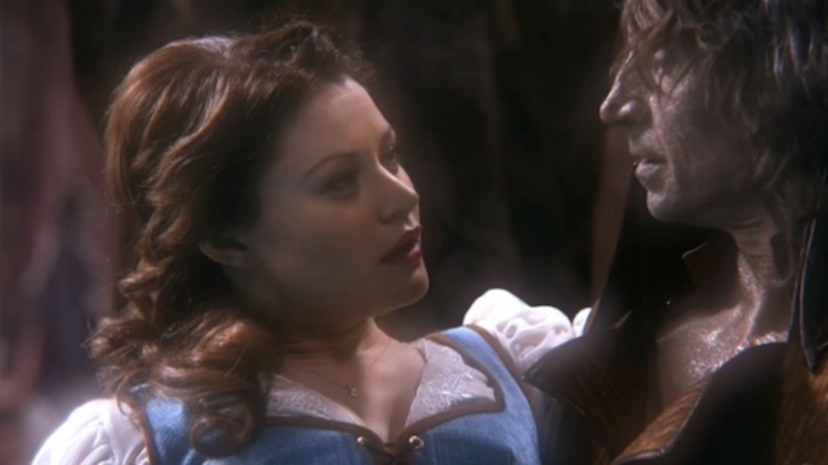 "A screen shot of the character Belle in ABC's show ""Once Upon a Time.""  They clearly paid homage to Disney's costumes, but made them more authentic to the time period portrayed in the show.  Here, the blue dress is designed as a more renaissance styl"