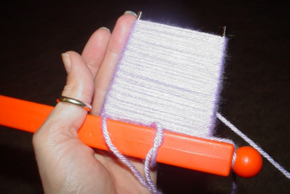 Secure the working yarn to the top ball and begin winding it around the pegs.