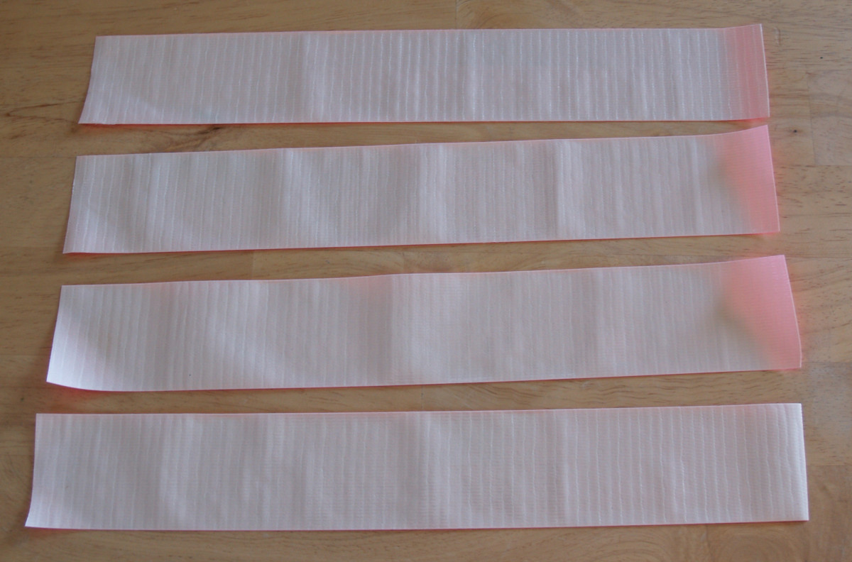 "Cut four strips of Duck® Tape 11' to 13"" long. Place the strips on your work surface with the sticky side up."