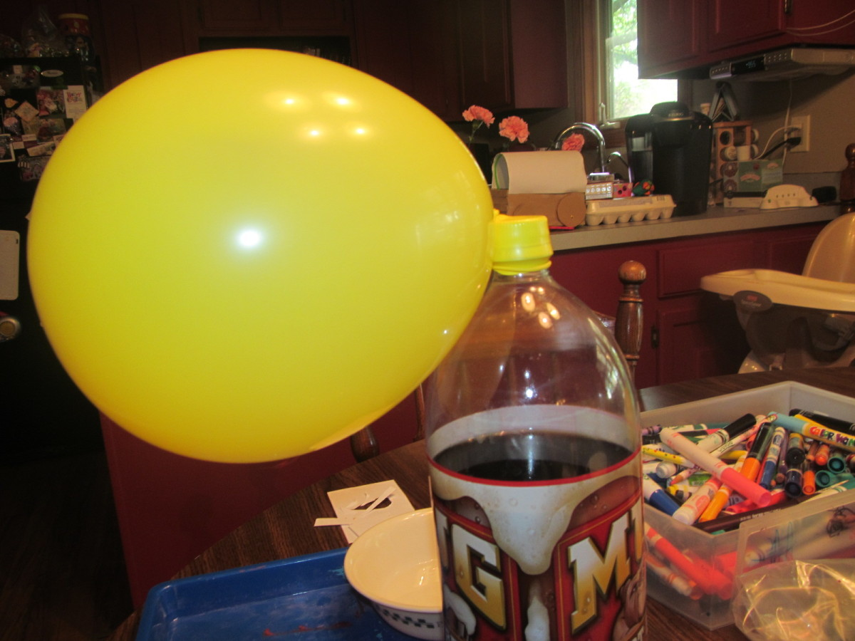 Carefully attach the end of the balloon to the top of a 2 liter bottle, it works better if the bottle is full of something so it is heavy and doesn't move.