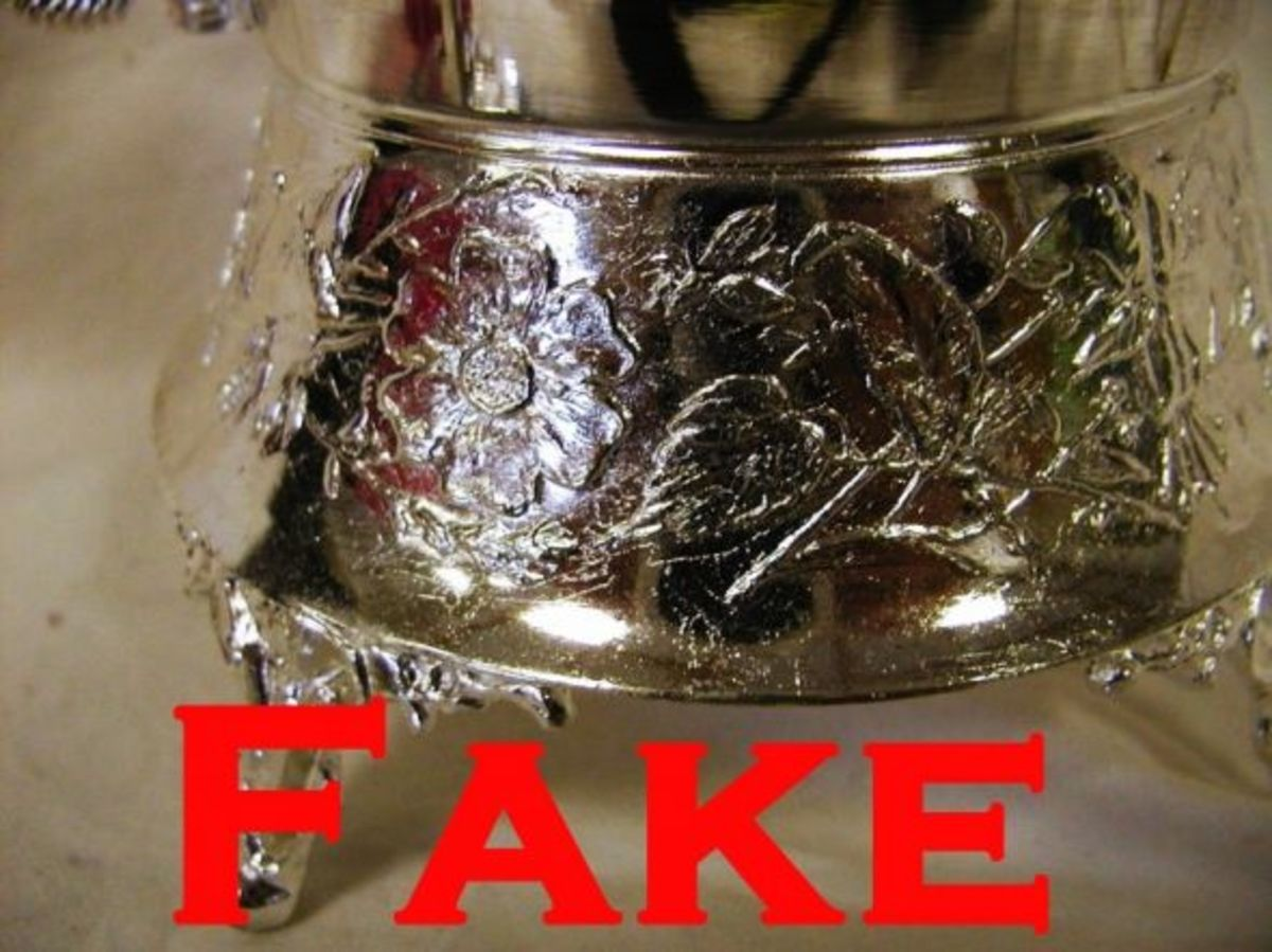 Base has messy, poorly defined decoration. Silver is flaky, and bubbly. Both are signs of reproduction fakes. the silver is also overly bright.