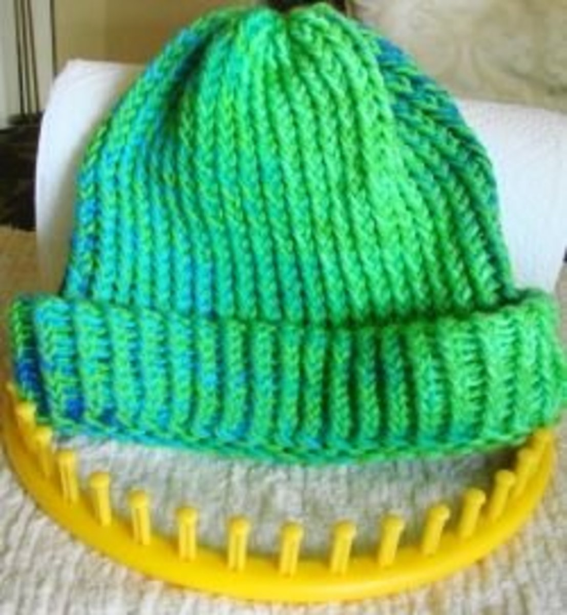 My favorite hat made with my yellow (XL) circular knitting loom and using solid color combined with variegated strands of acrylic 4-ply worsted weight yarn.