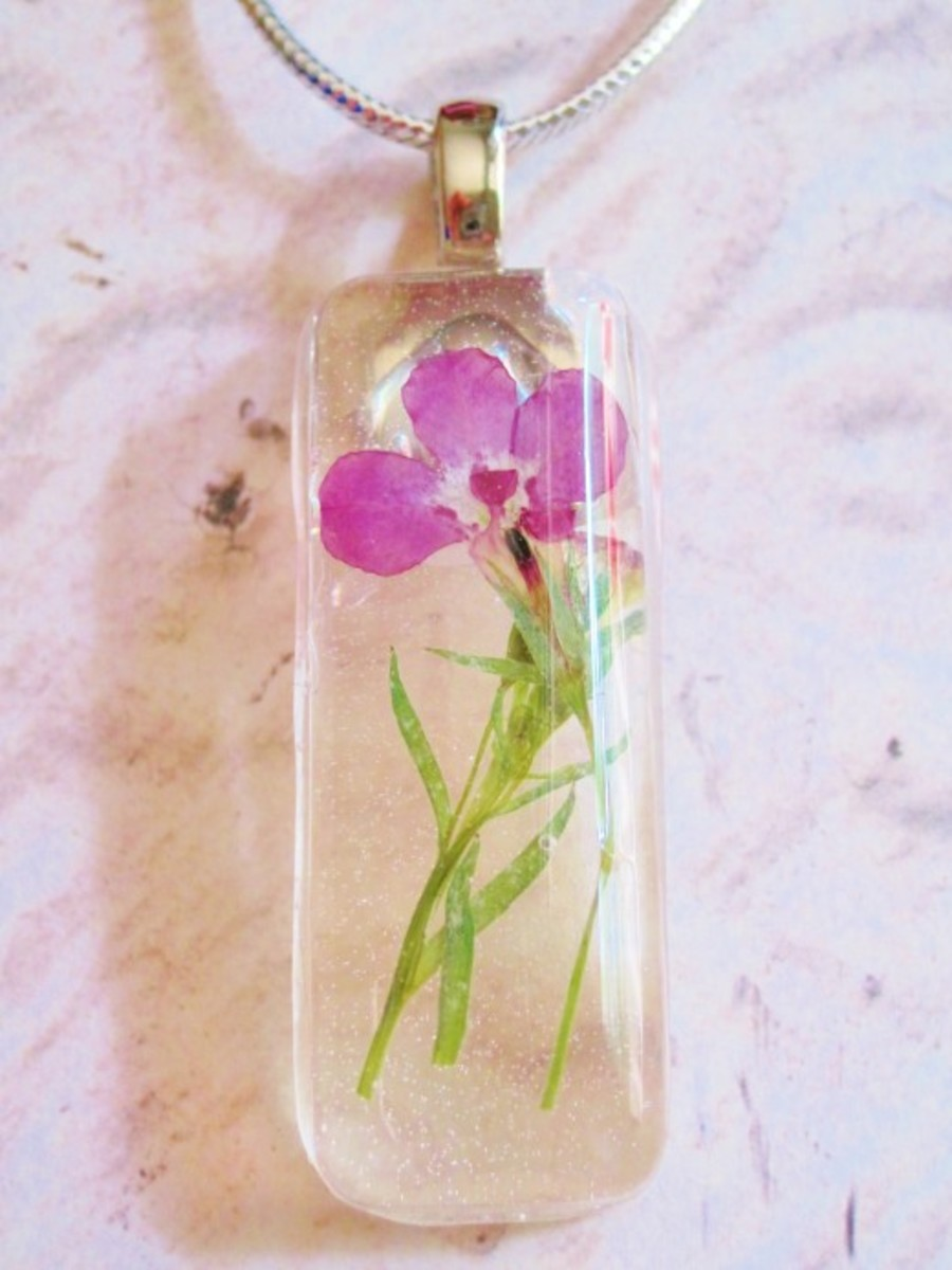 A finished botanical resin necklace.