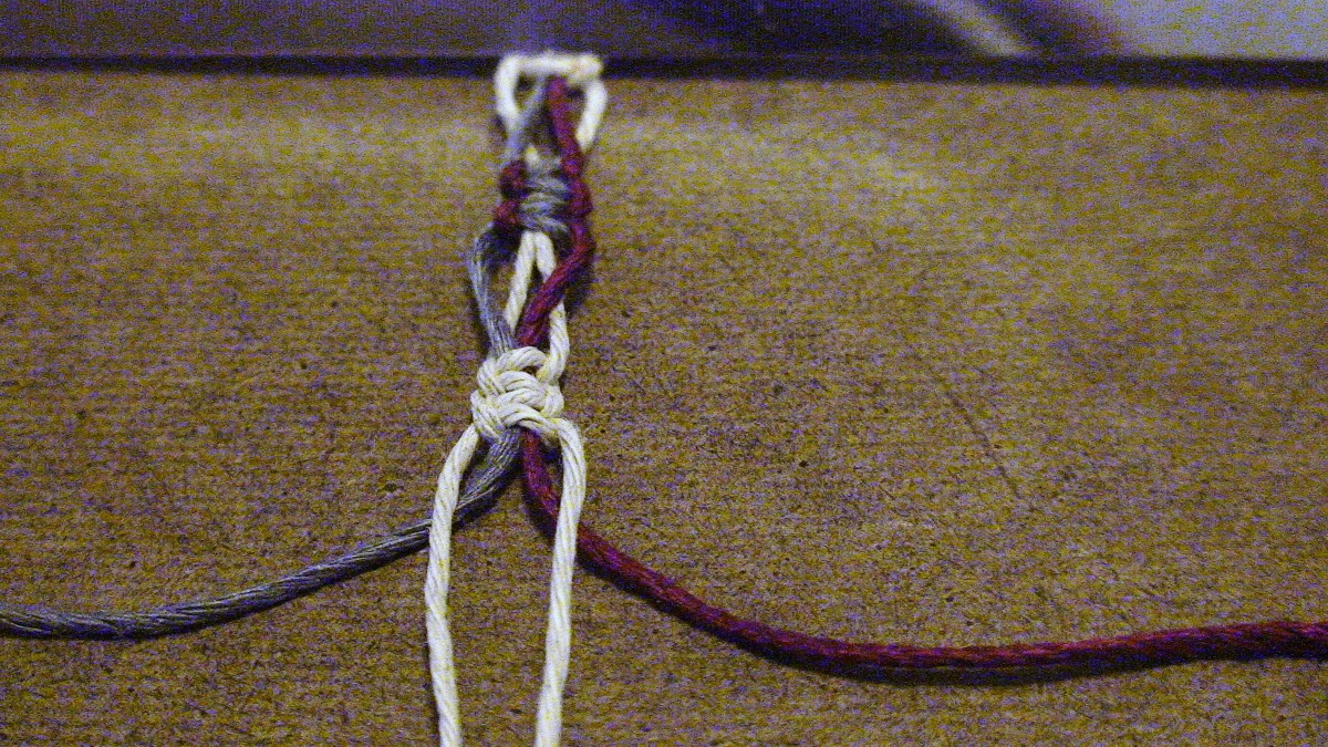15.  To make the next switch knot, begin by spreading the inner red/blue filler cords.  Pull down the beige cords.  They become the filler cords.