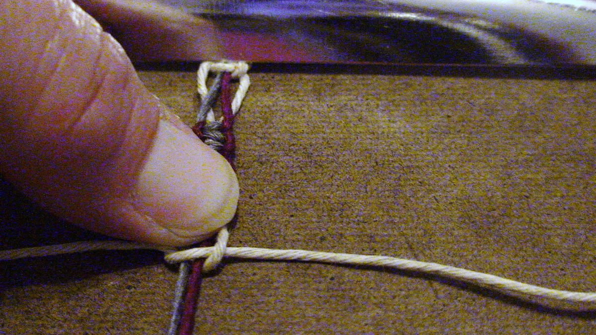 11.  Use your thumb to mark out a thumb's space and pull right half knot to that point.