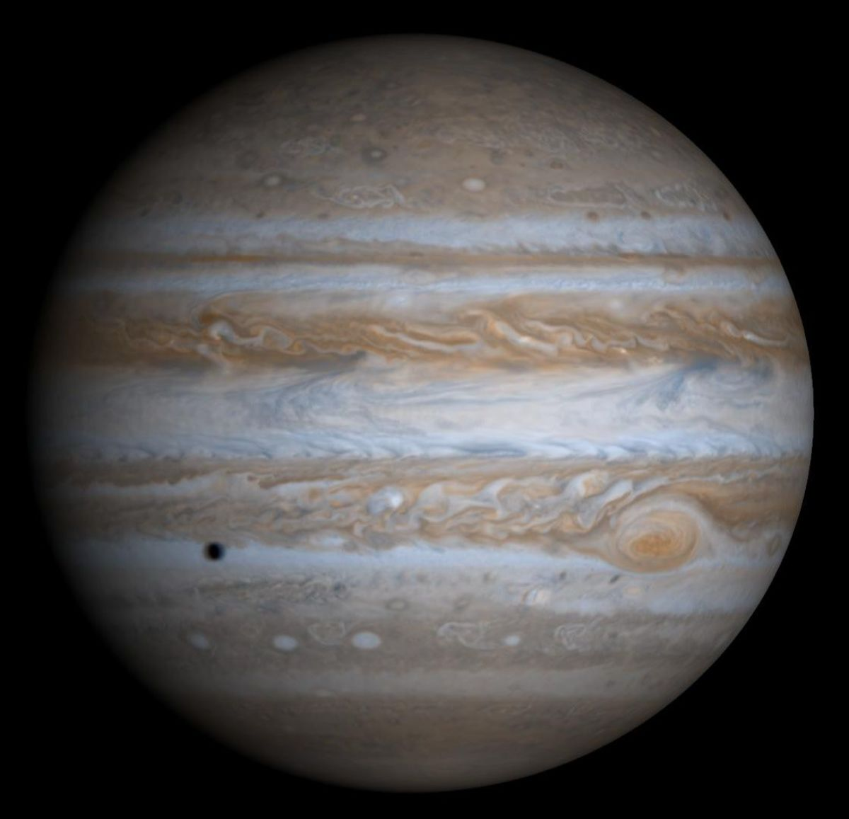 The largest planet in our solar system. You can see the shadow of Europa in the bottom left. Jupiter is one order of magnitude smaller than the Sun, and one order of magnitude larger than Earth.