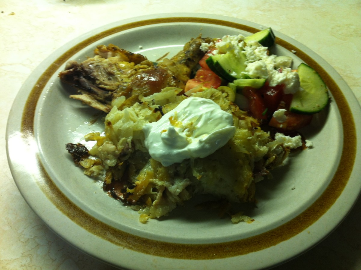 Kugelis topped with sour cream, chicken and side salad.