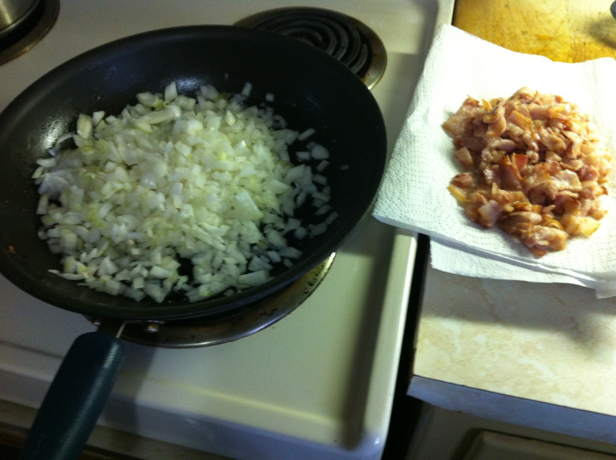 Bacon is draining on paper towels while chopped onions are cooking.