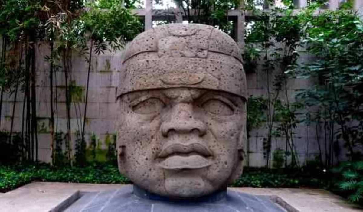 Olmec head with flattened facial features, epicanthal eye folds, and prominent lip groove (partial cleft palate)