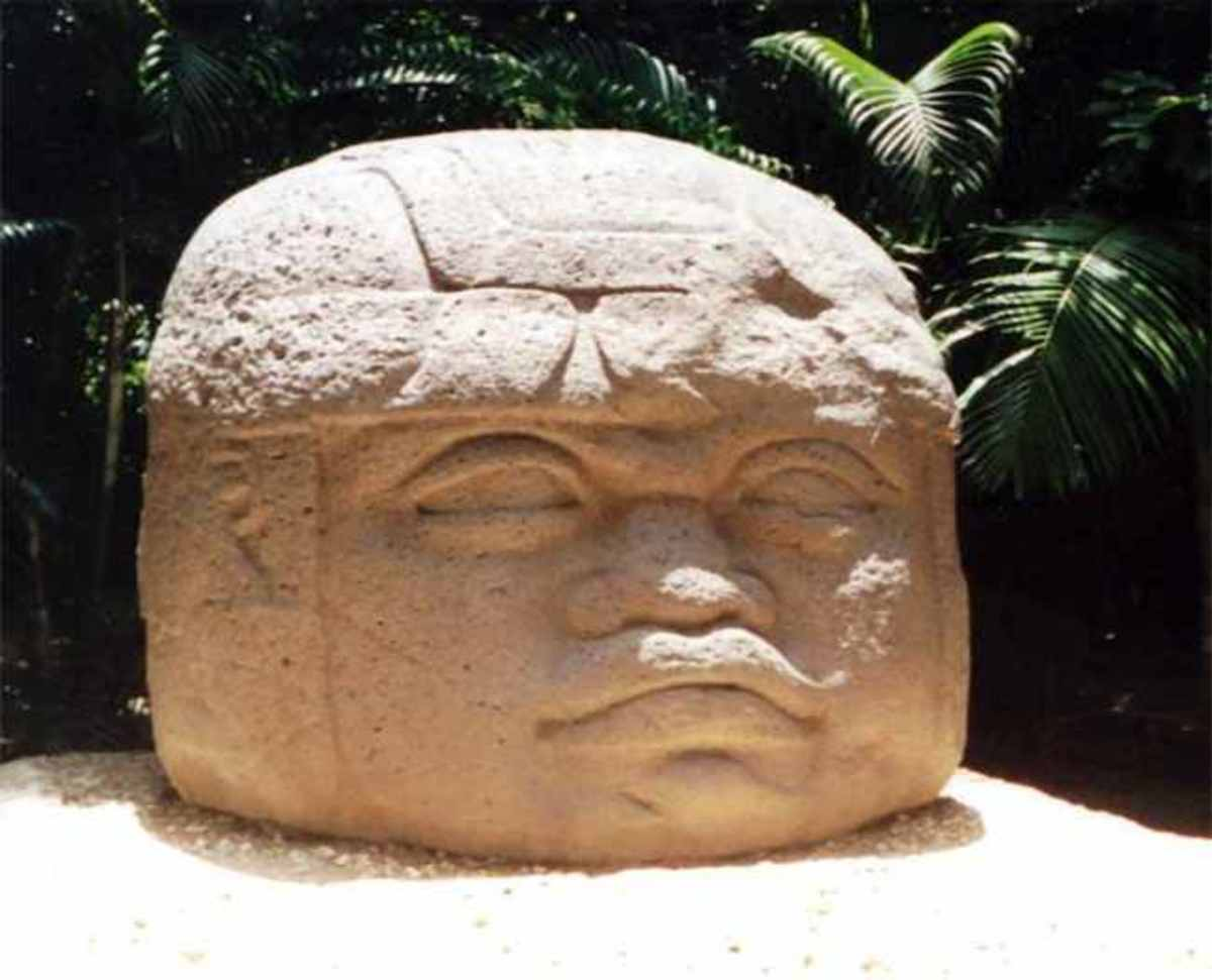 Olmec head with flattened facial features and protective helmet.