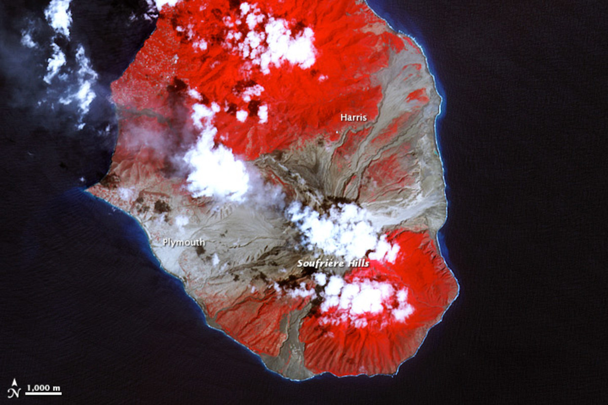 """This false-color satellite images show the southern half of Montserrat on March 17, 2007...Red areas are vegetated, clouds are white, blue/black areas are ocean water, and gray areas are covered by flow deposits.""  Credit: NASA"