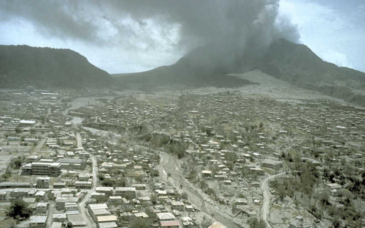 """On August 3, about 3 weeks after this image was taken, the first significant pyroclastic flow swept through the evacuated town.""  Photo by R. P. Hoblitt"