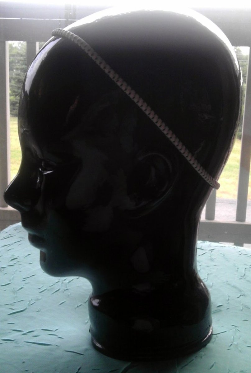 Ceramic head modeling an elastic headband with rubber grips.