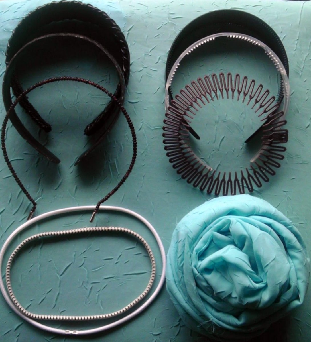 A selection of modern headbands. Clockwise from left: pleather, faux alligator, beaded wire, plastic with teeth, patterned with teeth, comb coil, elastic, elastic with grips, scarf