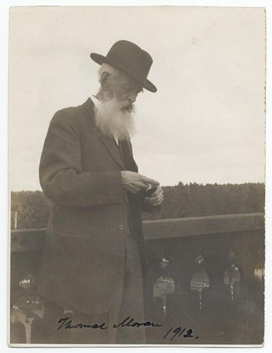 "Moran standing on a balcony, smoking a cigar. Inscription lower left: ""Thomas Moran, 1912"". Moran, Thomas, 1837-1926"