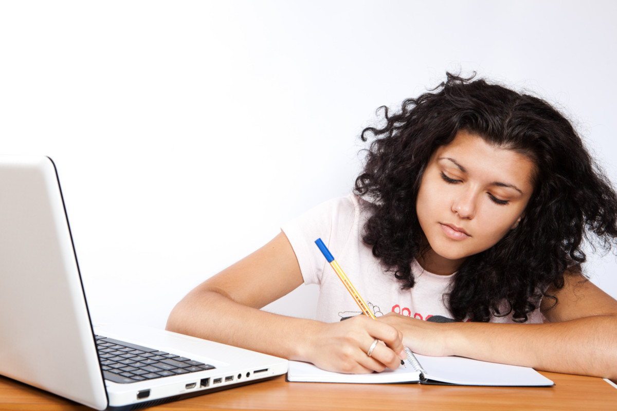 A student using modern technology and a simple notebook at the same time