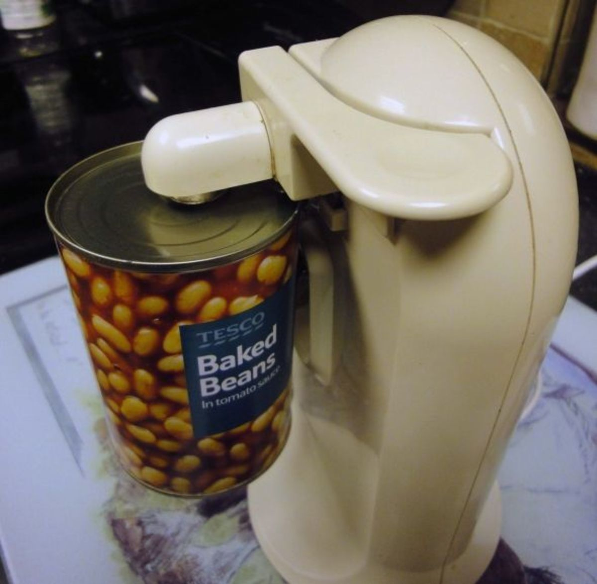 Firmly holding tinned food in electric can opener