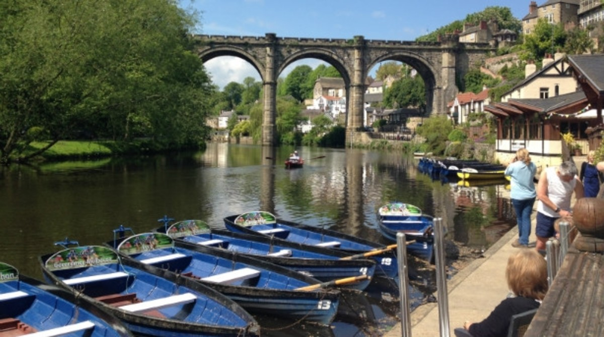 The riverside at Knaresborough with rowing boats and the 19th Century railway viaduct behind
