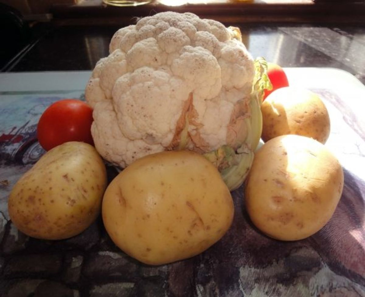 Ingredients for cauliflower cheese with baked potato and tomato