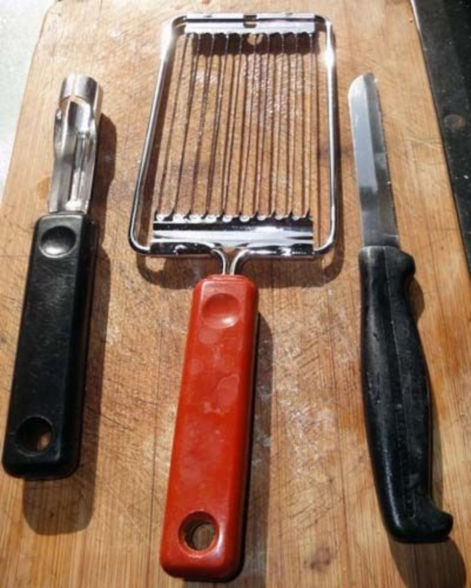 Kitchen Utensils for preparation of the dish including potato peeler, tomato slicer and sharp kitchen knife.