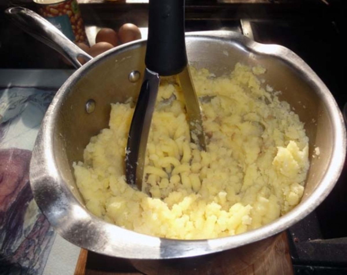 Mashing the potatoes with a good quality potato masher.