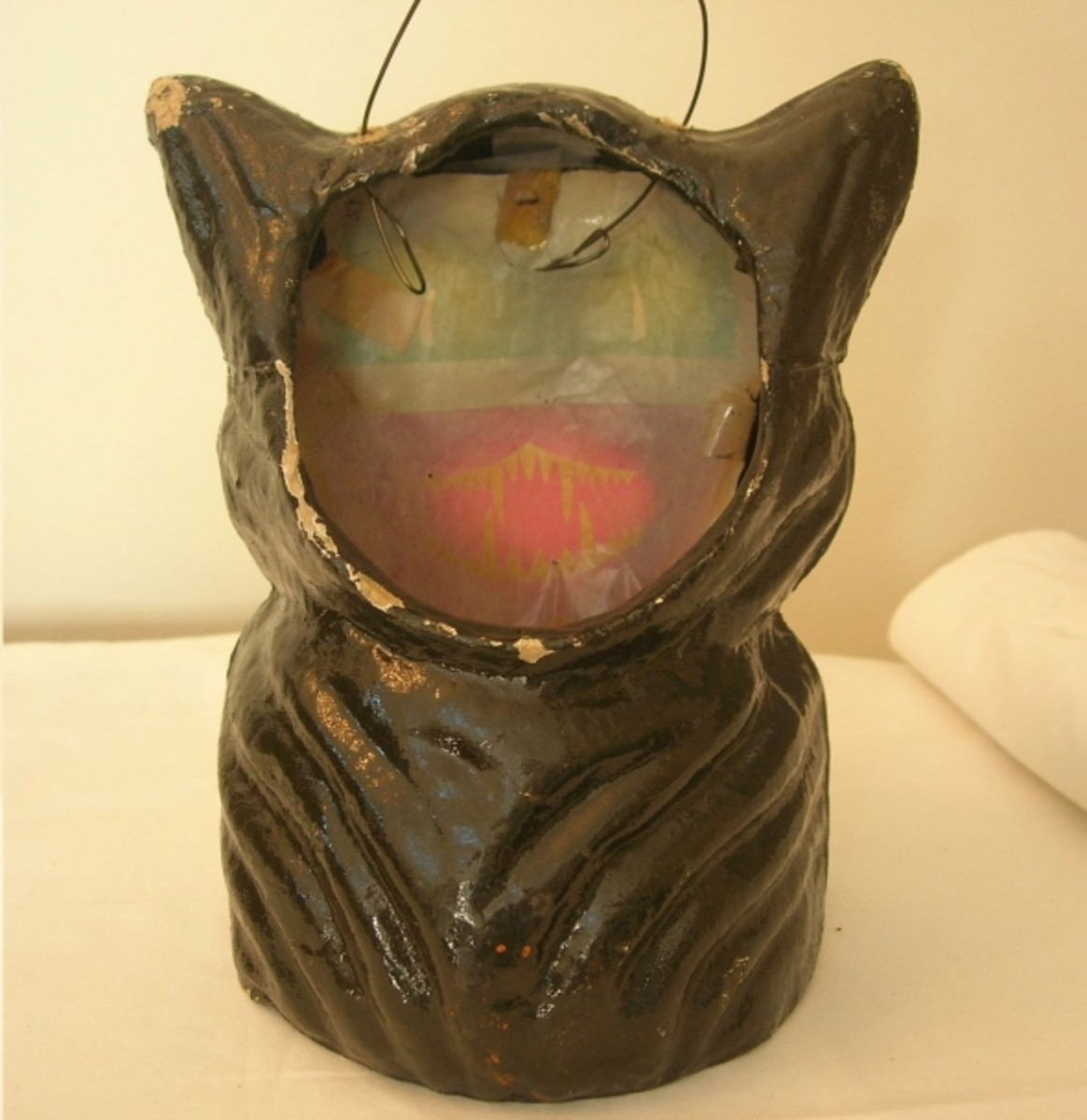 Inside the paper mache cat, a piece of paper would be taped that had the eyes and mouth design printed on it.